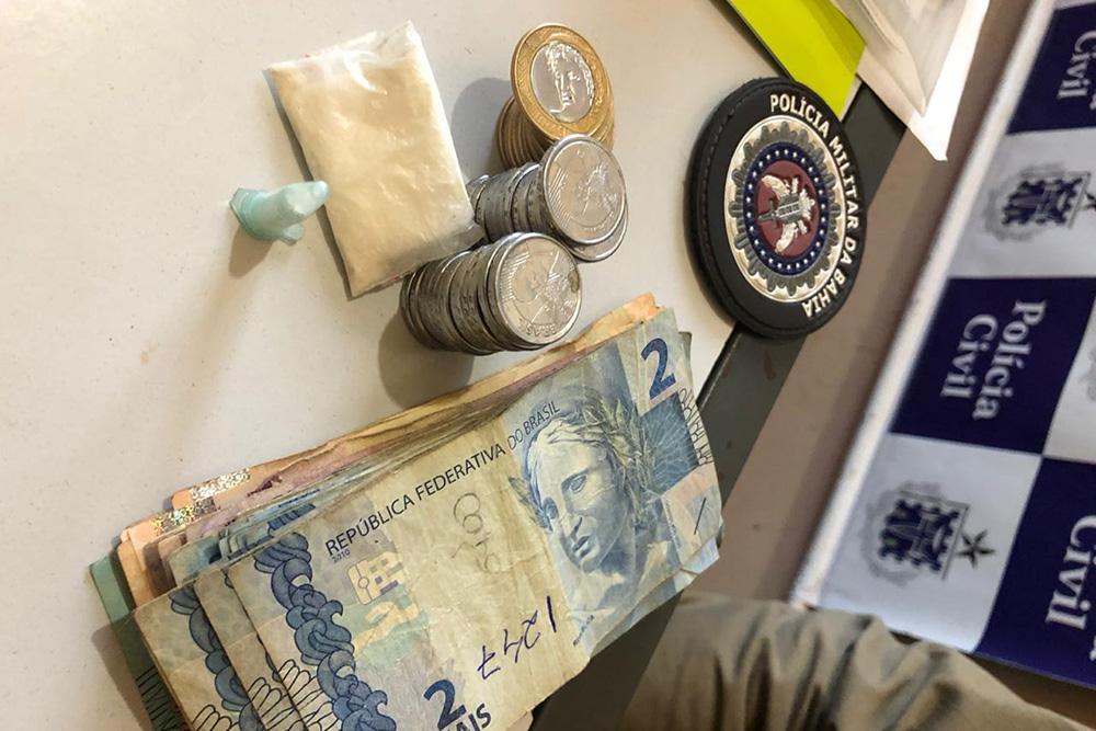 """De acordo com a polícia, a guarnição teve acesso à residência do suspeito e lá os policiais encontraram 1 pino e 1 """"sacolé"""" de pó, contendo substância análoga à cocaína, e também o valor de R$1274,00 (mil duzentos e setenta e quatro reais) em espécie."""